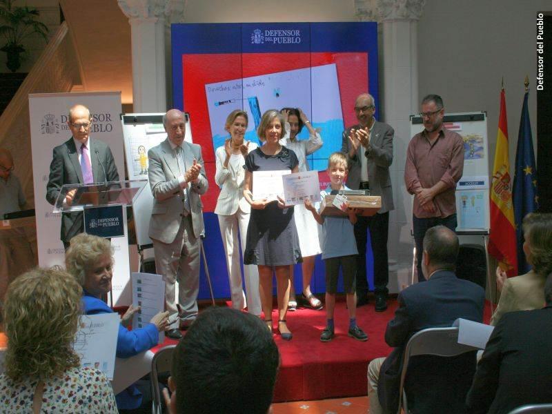 Uno de los ganadores y su profesora recoge su premio ante la mirada del jurado del Concurso de Dibujos