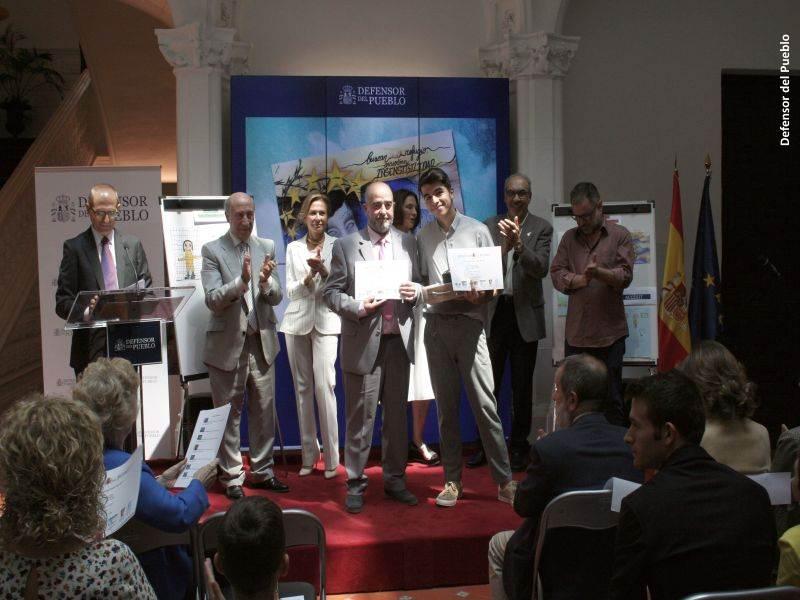 Uno de los ganadores recoge su premio ante la mirada del jurado del Concurso de Dibujos