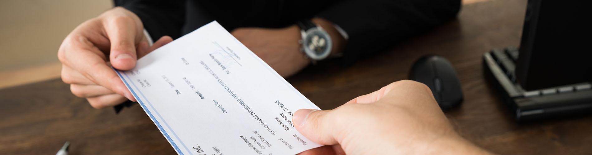 Unas manos muestran un cheque bancario