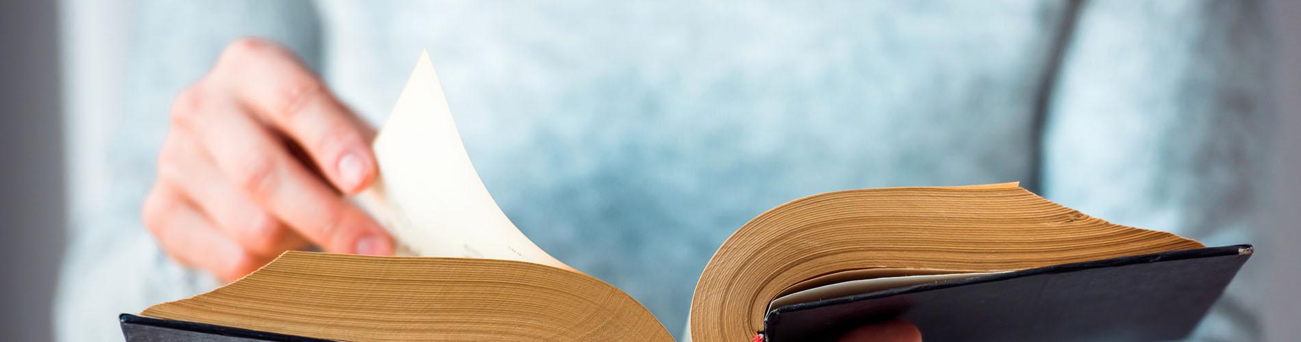 Manos ojeando libro