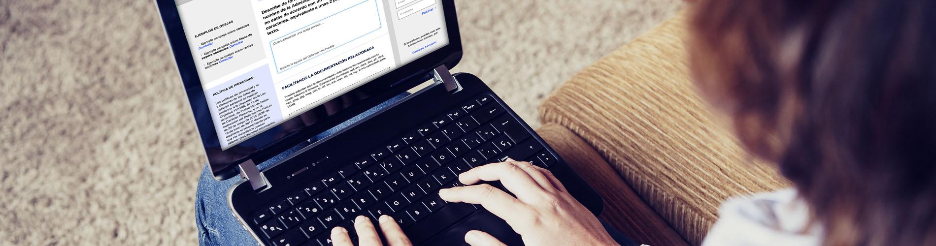 Persona de espaldas tecleando en un ordenador portátil