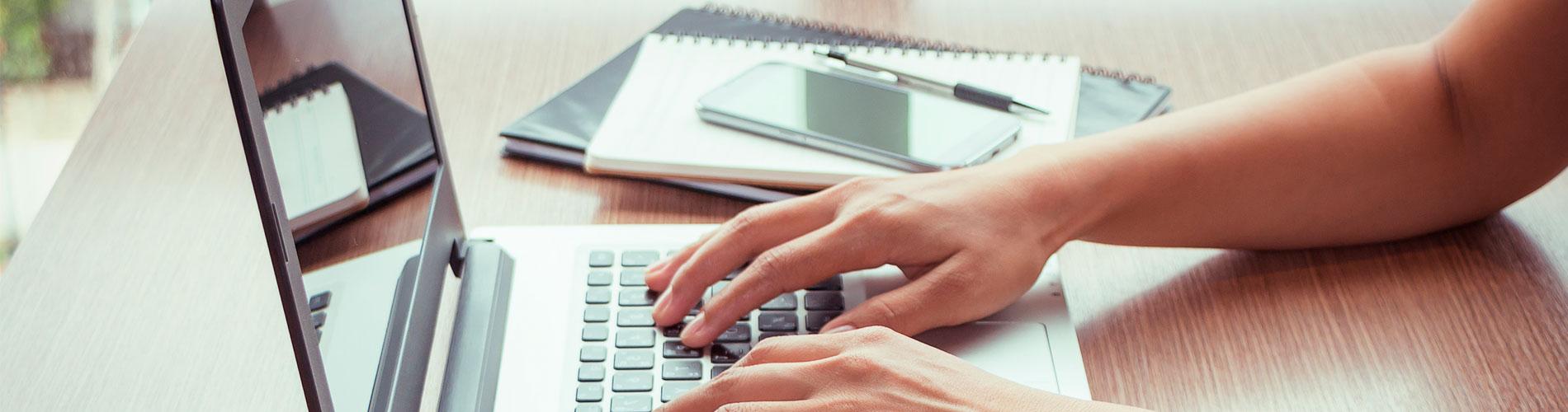 manos tecleando sobre un ordenador portátil. Junto a él, unos cuadernos, un móvil y un bolígrafo