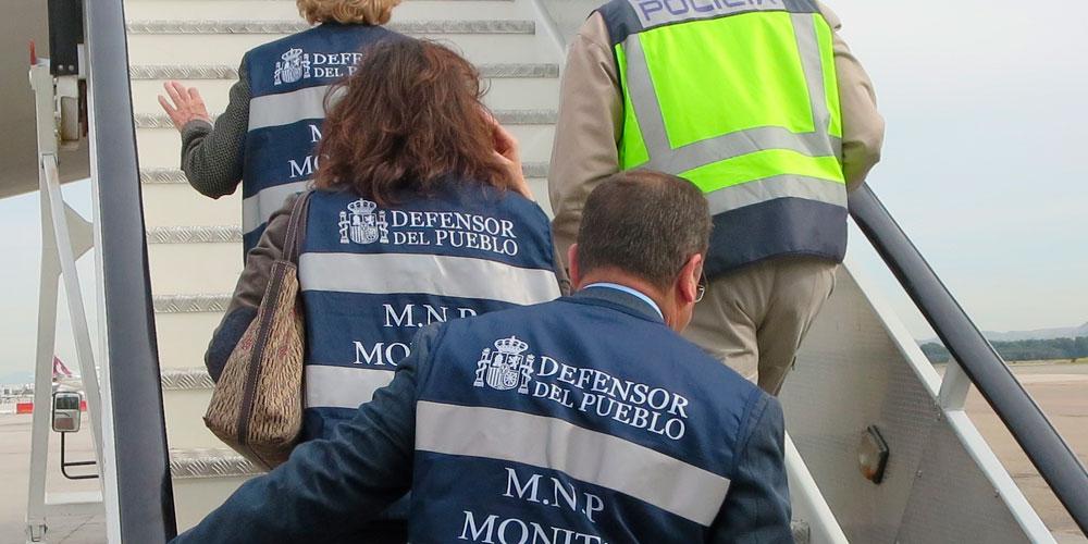 Tres miembros del MNP del defensor del pueblo suben una escalinta de un avión junto con un policía