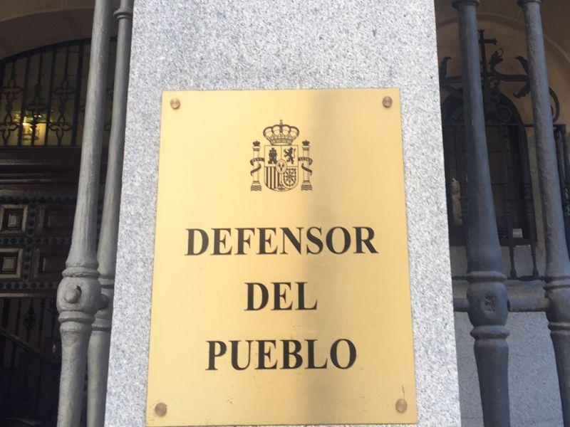 Placa dorada con el escudo y texto EL Defensor del Pueblo en la fachada de la institución