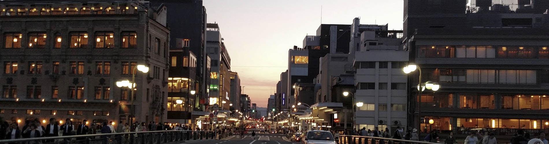 Calle de una ciudad al atardecer, iluminada, con tráfico y transitada