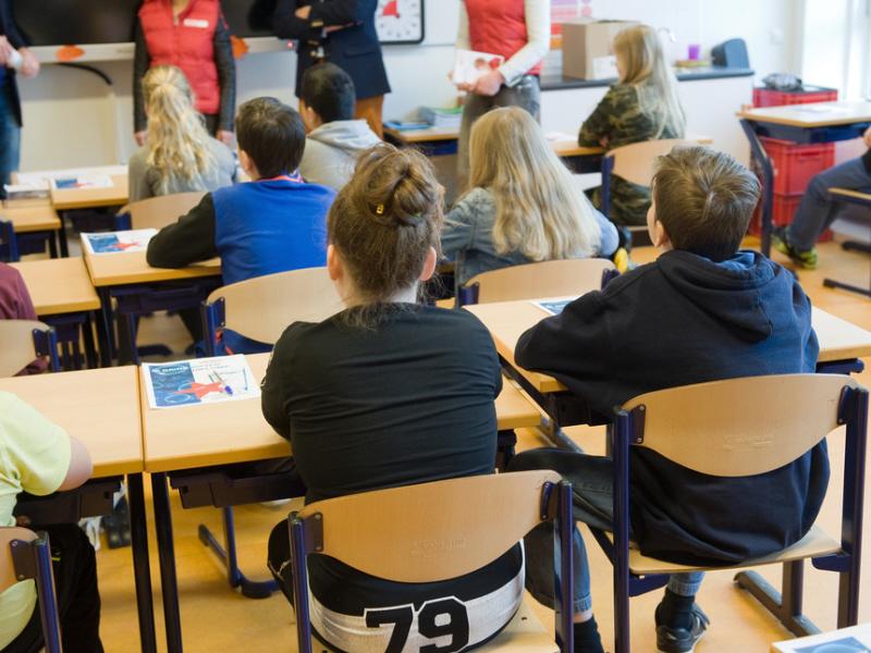 aula profesora explica, alumnos en sus mesas escuchando