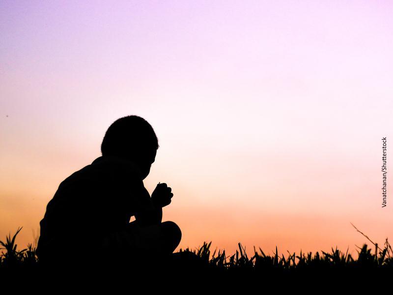 niño sentado sobre la hierba y con el anochecer de fondo