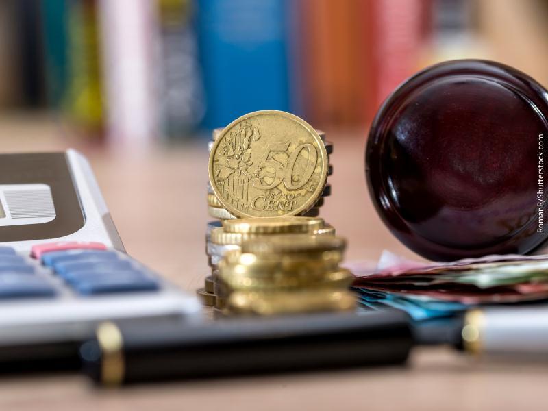 Calculadora, monedas y billetes de euro y maza de juez