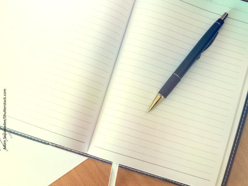 Agenda abierta en blanco para anotar con bolígrafo que está encima