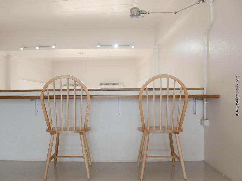 Dos sillas de madera clara frente a mostrador blanco