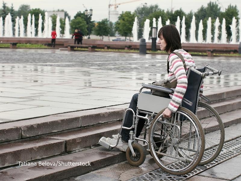 Chica en silla de ruedas frente a unas escaleras de acceso a un parque público