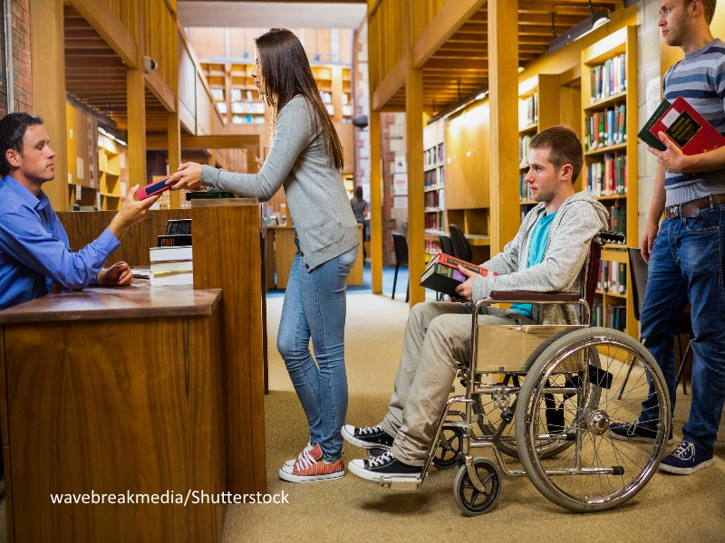 Estudiantes en biblioteca en silla de ruedas