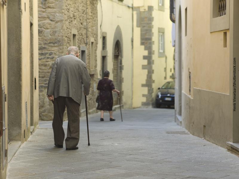 Pareja de ancianos caminando el hombre detrás de la mujer apoyados en bastones