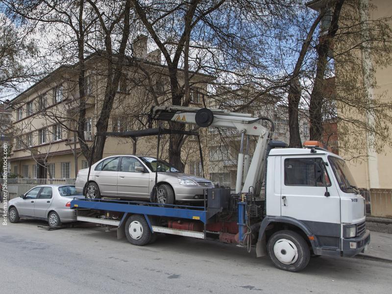 Grúa llevándose coche mal aparcado en calle pequeña