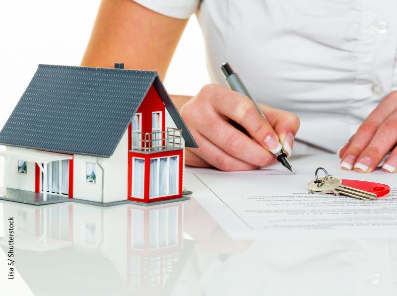 Persona firmando documento e imagen de casita