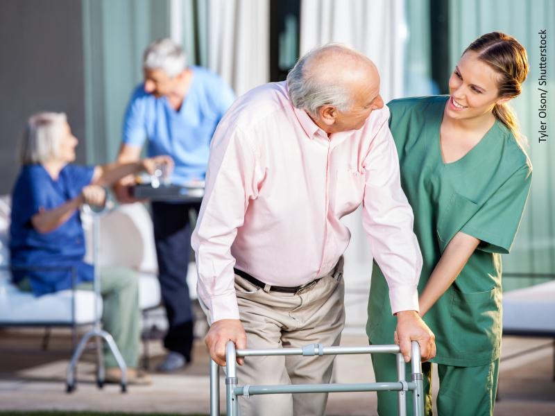 Auxiliar ayudando a persona mayor