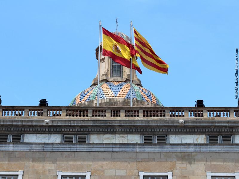Banderas española y catalana ondeando sobre edificio barcelonés