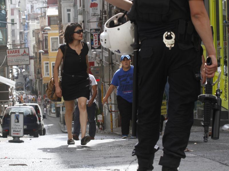 Policía de espaldas vigilando calle concurrida