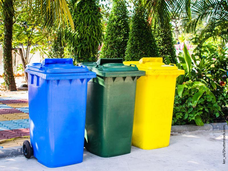 Contenedores de basura amarilla, verde y azul, en parque soleado.