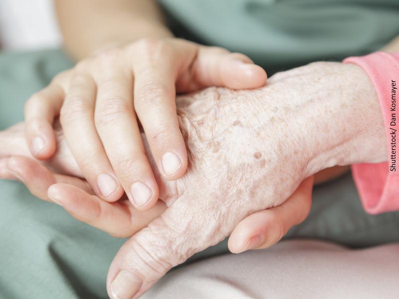 MMano de persona mayor sujetada por las manos de un cuidador