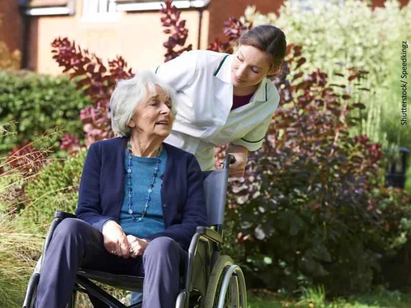 enfermera empujando silla de ruedas en la que está una mujer mayor
