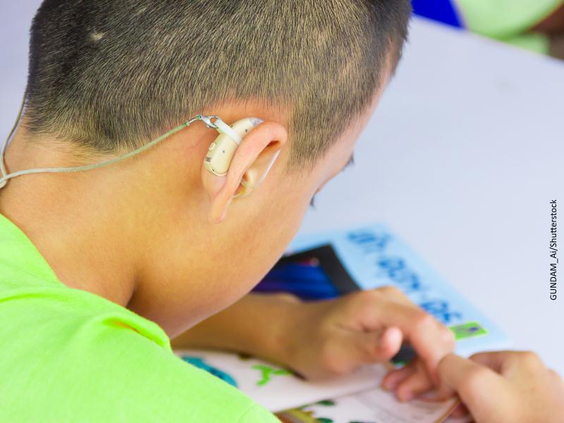 niño con aparato para audición