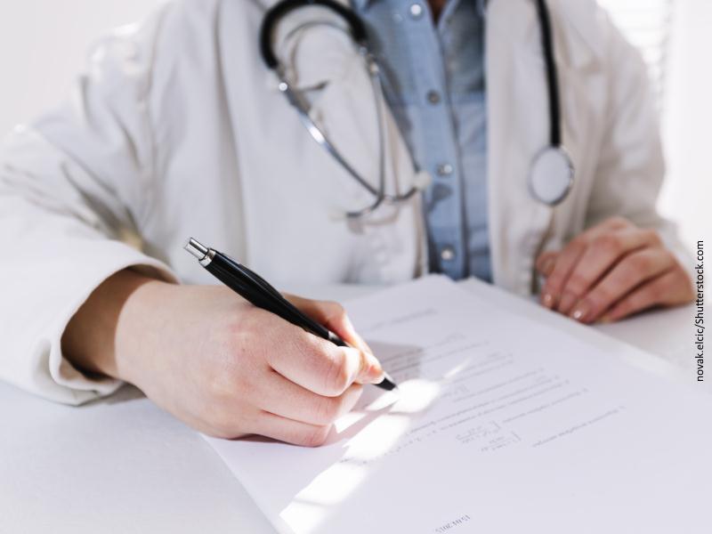 Médica escribiendo en consulta