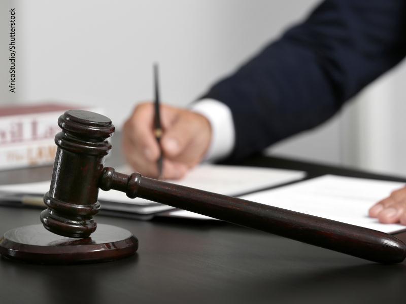 Maza de juez en primer término de una mesa en la que un hombre escribe