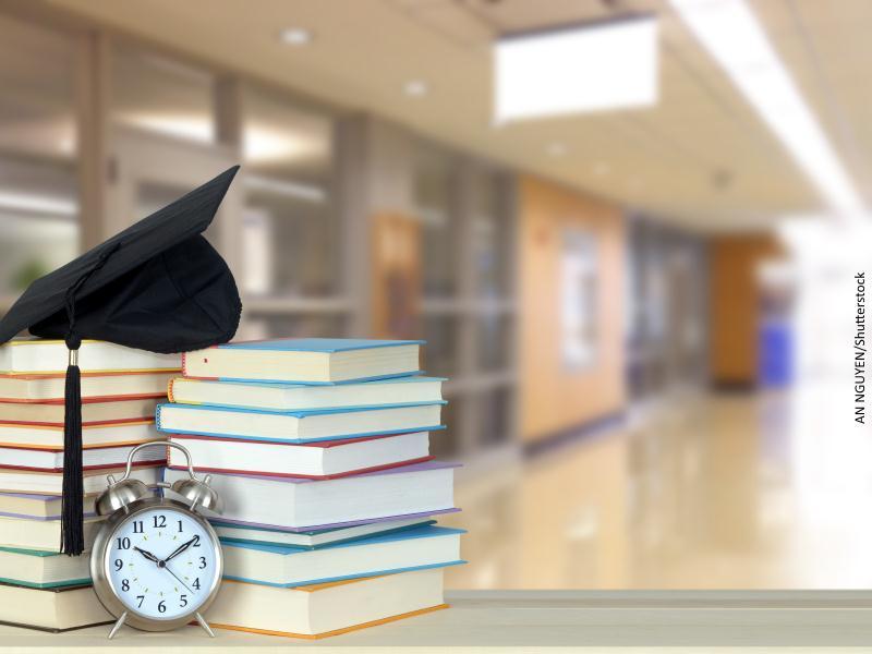 Birrete sobre libros y despertador con fondo de pasillo con despachos modernos
