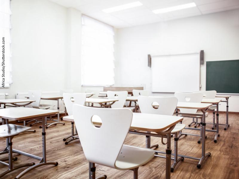Aula vacía con pupitres y sillas blancas, pantalla y pizarra al fondo