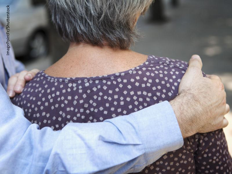 Mano de hombre coge por el hombro a mujer mayor