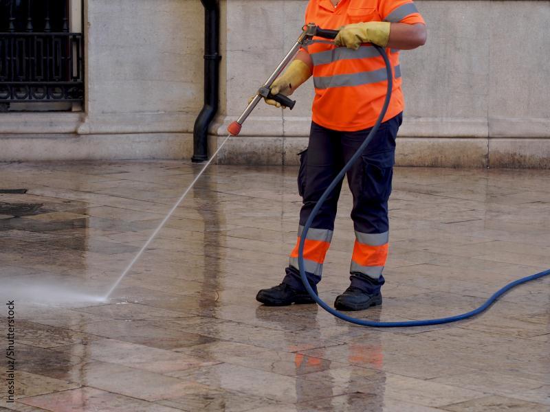 Persona con uniforme naranja limpiando acera con chorro de agua