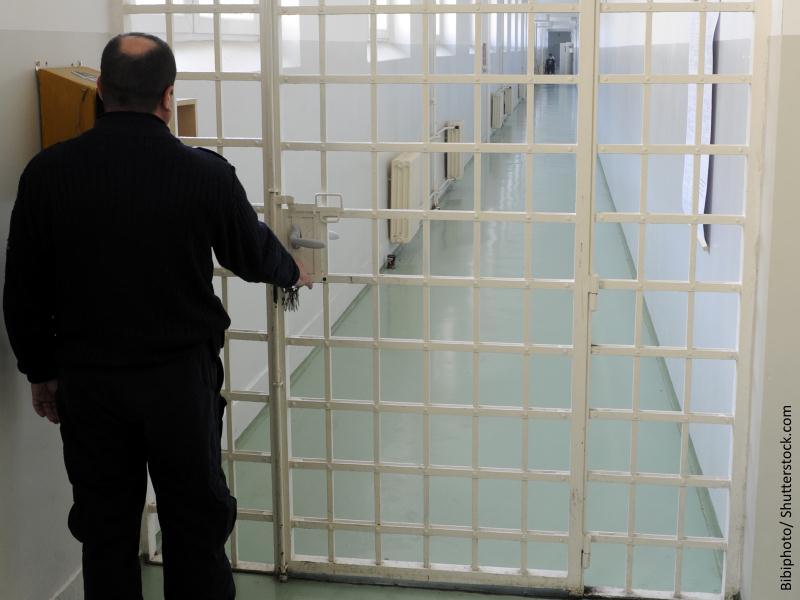 Funcionario de prisiones de espaldas abriendo una reja