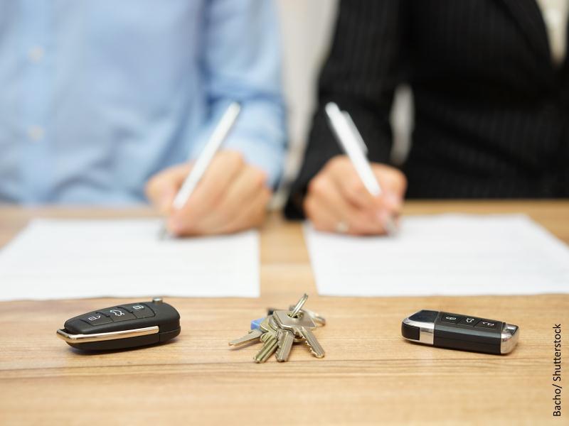 Personas firmando documentos y llaves de casa y coche sobre la mesa