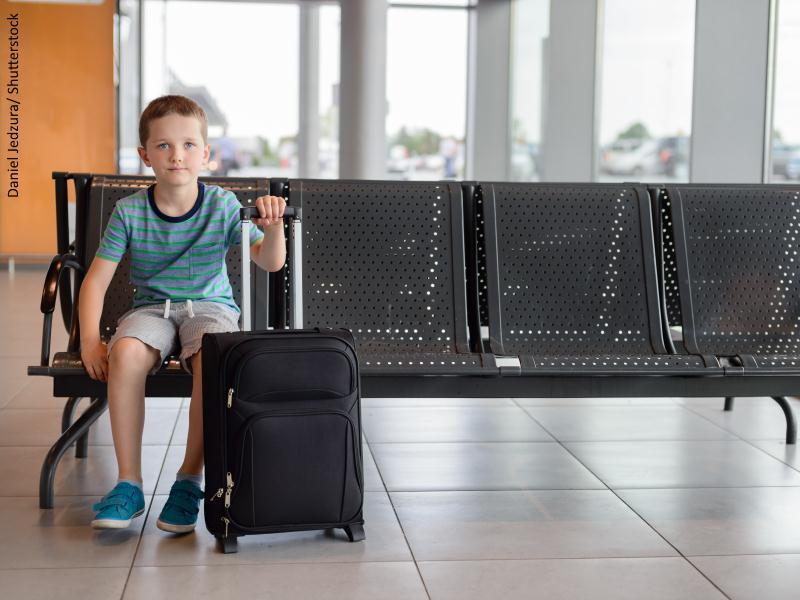 Menor con maleta sentado en un banco