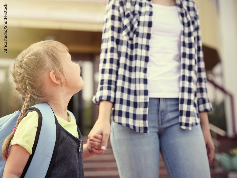 Mujer dando la mano a niña con mochila escolar