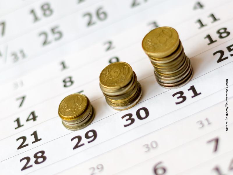 Tres montones de monedas de euro apiladas sobre hoja de calendario
