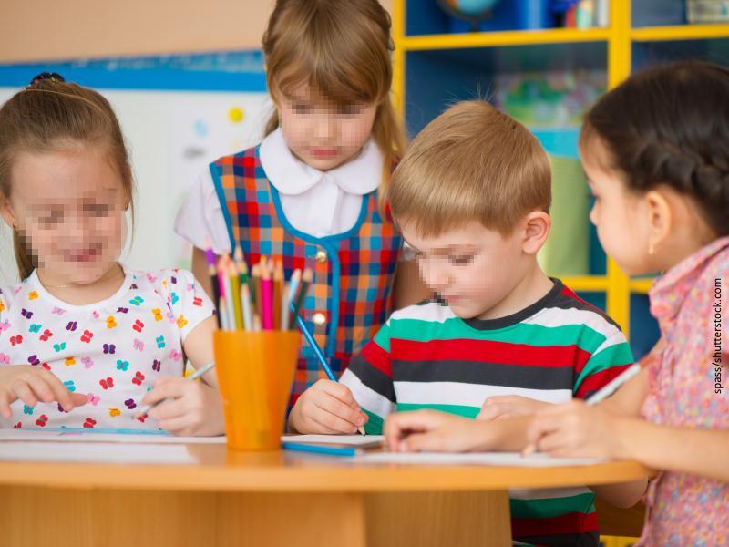 Tres niñas y un niño en escuela infantil dibujando