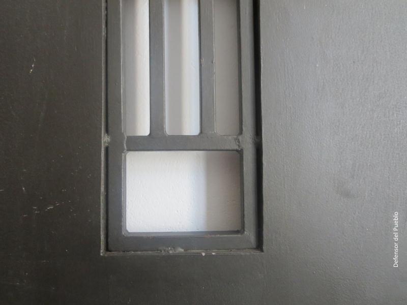 Ventanuco con rejas en puerta de celda pintada de gris