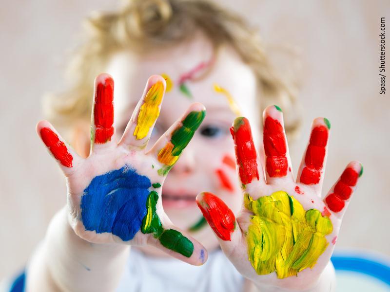 niño con manos pintadas de colores
