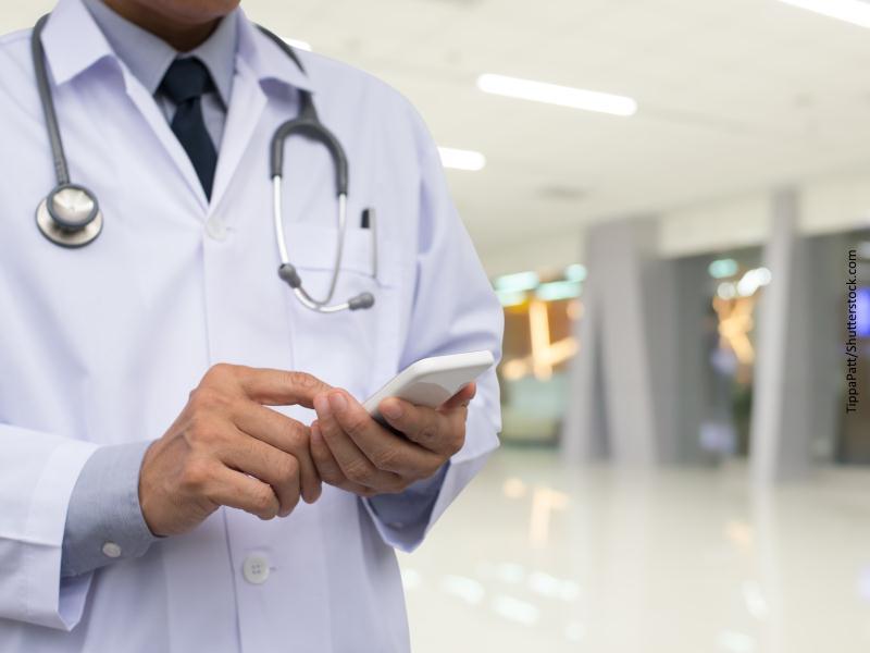 Médico haciendo anotación en teléfono móvil