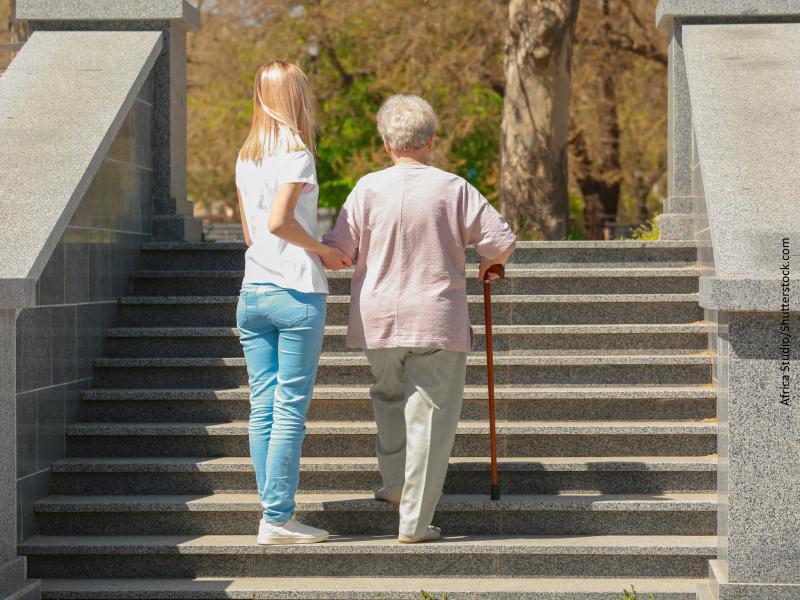 Mujer joven ayuda a mujer mayor subir escaleras