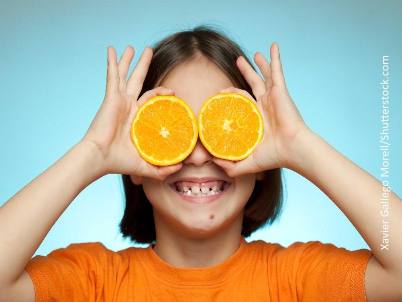 Niña con medias naranjas sobre los ojos