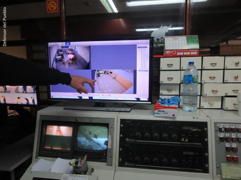 Mano que señala una de las pantallas con imágenes de las cámaras de vigilancia de las celdas