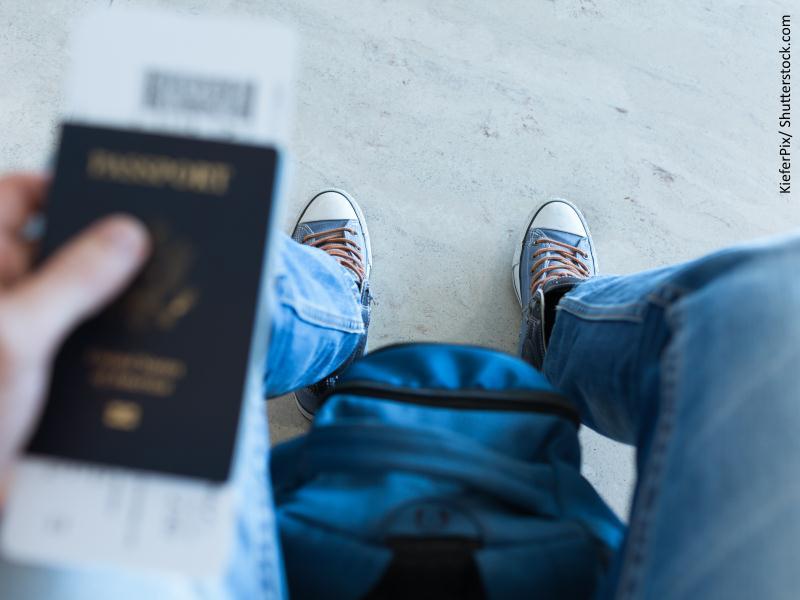 Un joven sositene en una mano su pasaporte con unos billetes de avión y entre sus piernas una mochila