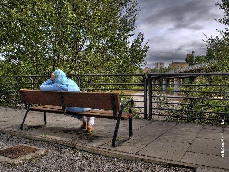 Mujer magrebí sentada en un banco vista de espaldas