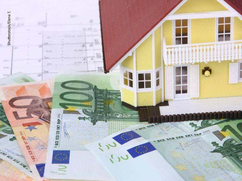 Billetes de 100 y 50 euros bajo una casa en miniatura