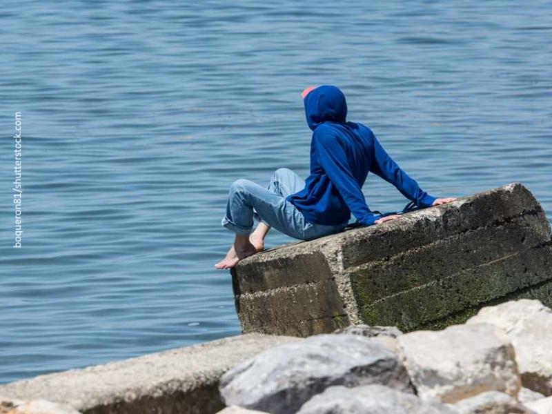 Joven contemplando de espaldas el mar