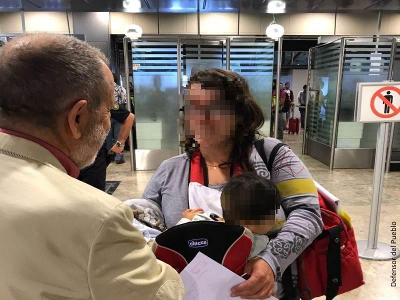 Francisco Fernández Marugán (Defensor e.f.) charla con una mujer que lleva un bebé en una mochila (ambos rostros pixelados) en el aeropuerto