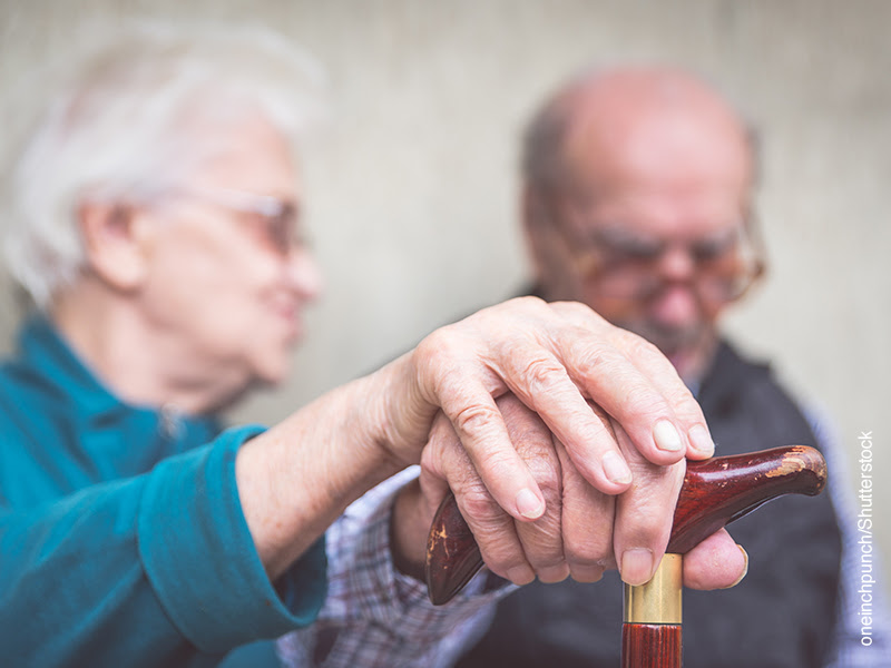 Una pareja de ancianos se superpone la mano en gesto de apoyo sobre el mango de un bastón
